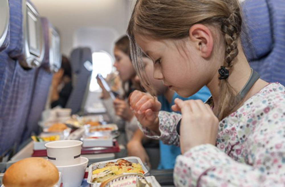 Girl about to eat airline meal --- Image by © PhotoAlto/Corbis